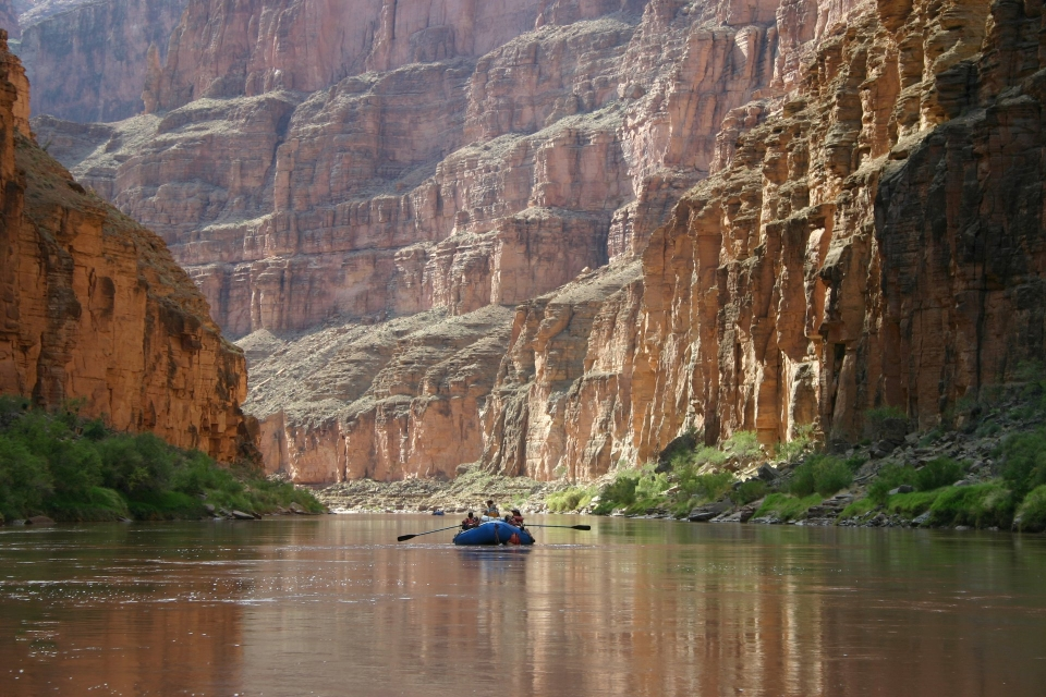 A blue raft floating on a stretch of calm Colorado River water, with vegetation along the shore. On all sides are towering vertical cliffs of stratified rock at Grand Canyon National Park.