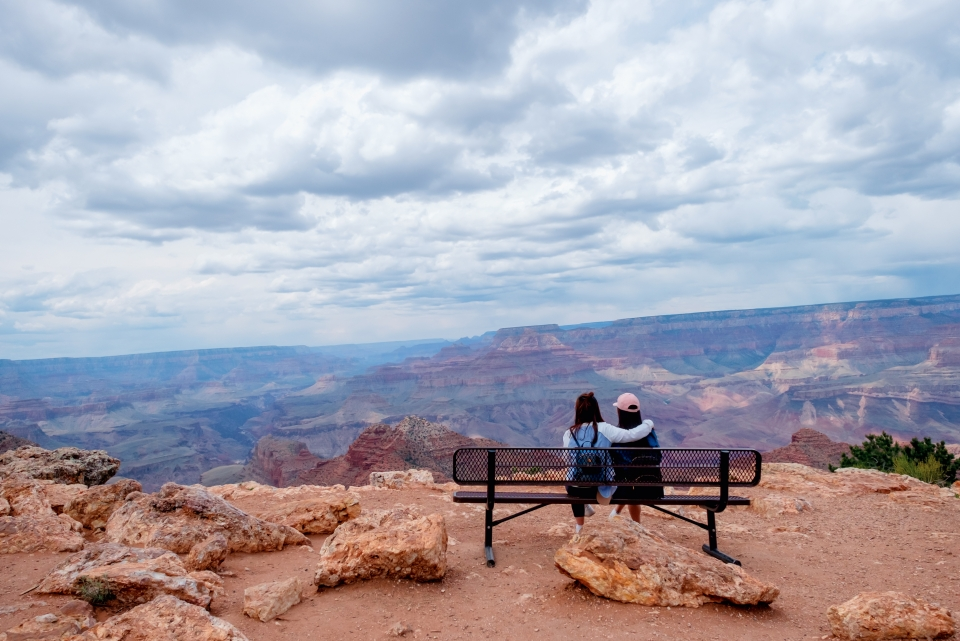 Two people sit on a bench, looking out over Grand Canyon National Park.