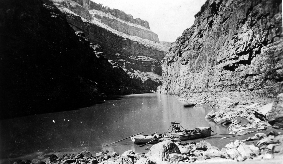 Vintage photograph of John Wesley Powell's chair strapped into a small rowboat, among the ridges and cliffs of Marble Canyon