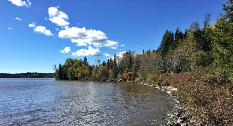 Sunny day along the rocky tree-lined coast of Lake Superior at Grand Portage National Monument