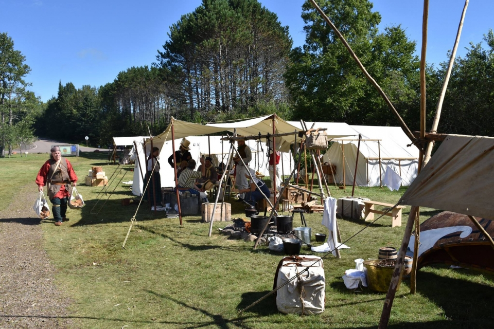 Historical enactment camp with canvas tents and people walking in period clothing at Grand Portage National Monument