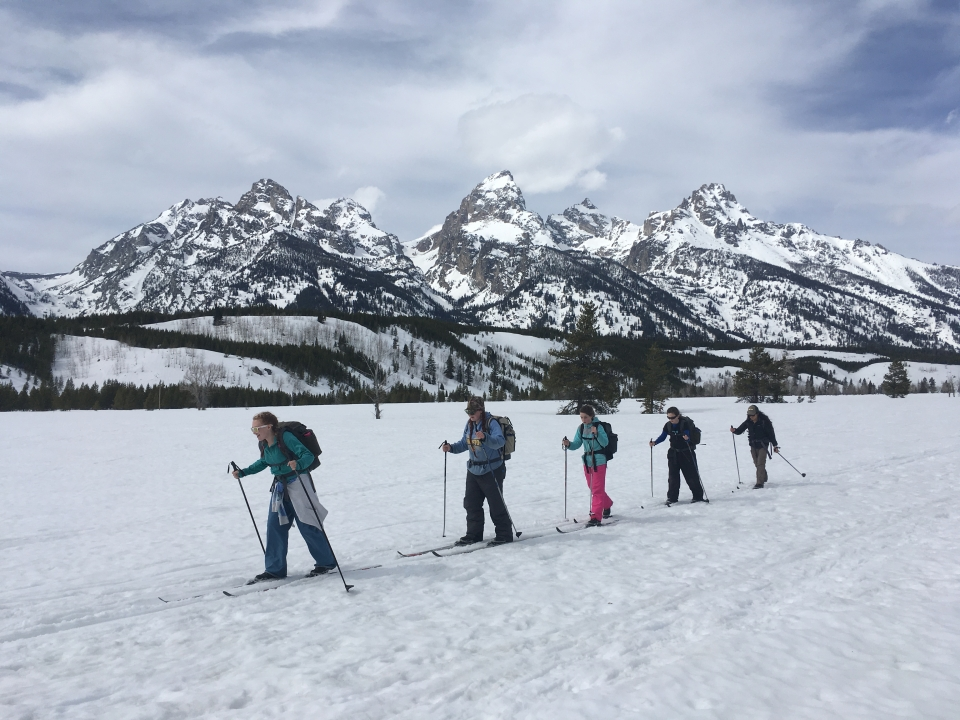 Five kids cross-country skiing with snow-covered mountain range in the back at Grand Teton National Park