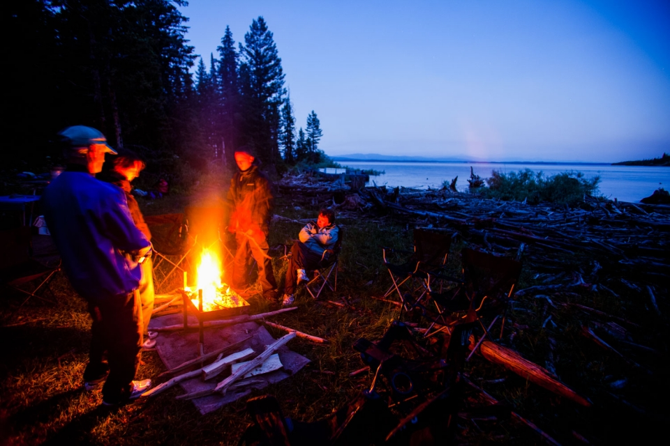 Four people sitting around a campfire at the edge of a lake at Grand Teton National Park
