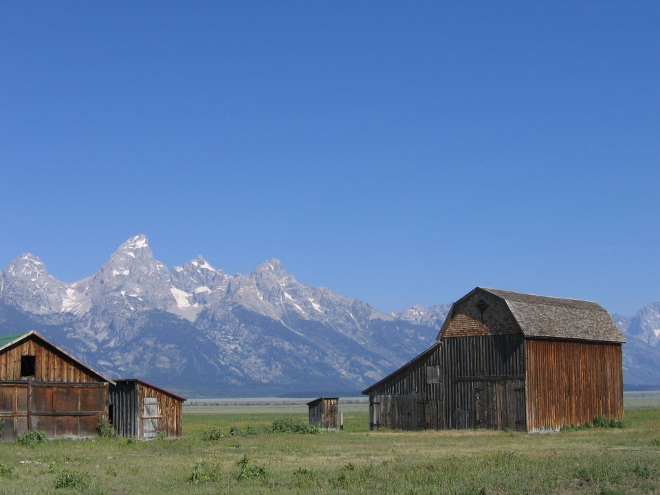 A couple of old wooden buildings in front of the granite mountains of the Teton Range
