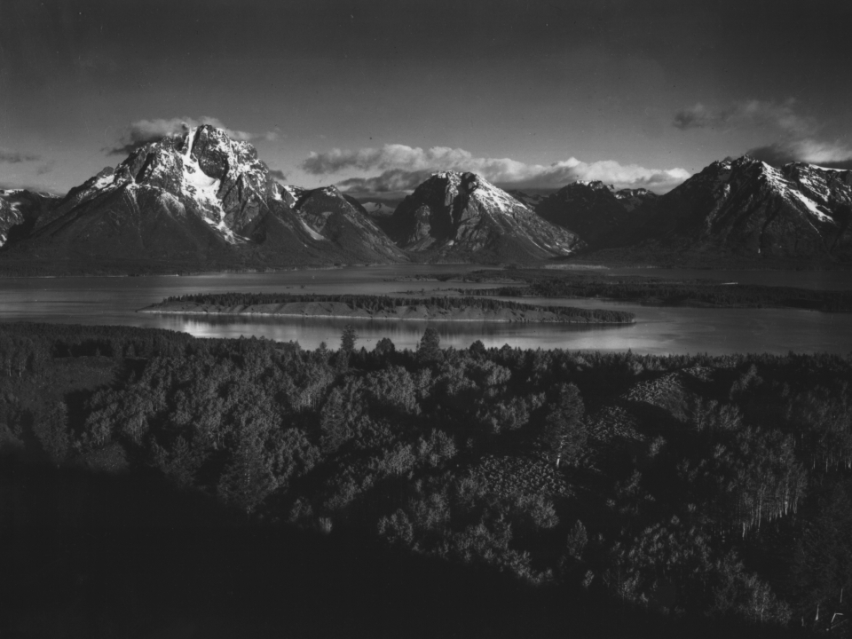 Black and white photograph of a snow-dusted mountains behind a lake at Grant Teton National Park by Ansel Adams