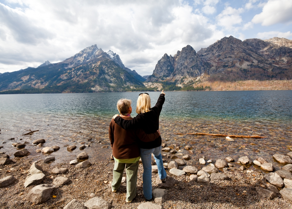 Two women looking out on Grand Teton National Park, one with her arm around the other and one arm pointing outwards.