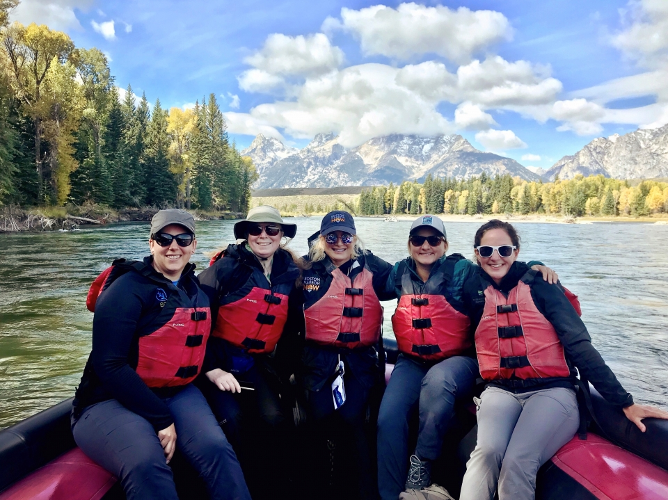 Five women gather and smile at the camera on a raft on a river, with a cascades of mountains in the background. They all wear sunglasses and safety floatation jackets.