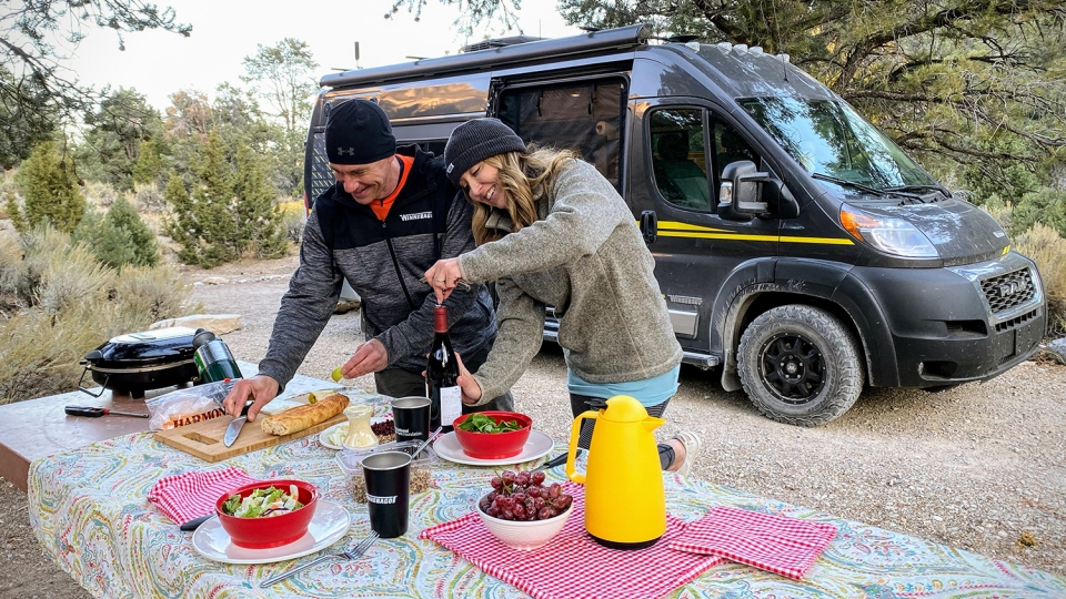 Two campers enjoy a picnic set up on a table next to their Winnebago in Great Basin National Park