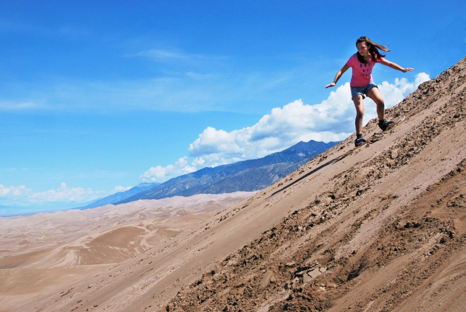 Girl in a pink shirt sandboarding on a sandy hill with mountains in the background at Great Sand Dunes National Park