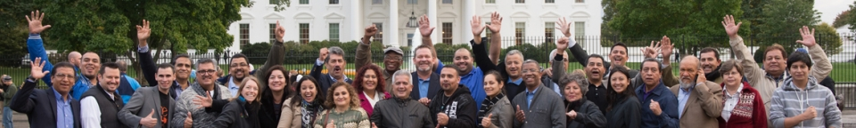A group of people pose in front of the White House, smiling and waving at the camera