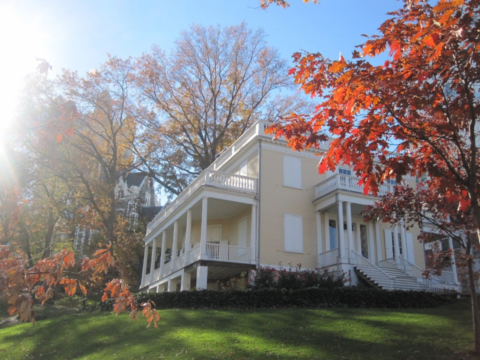 The yellow house of Hamilton Grange National Monument with red autumn leaves