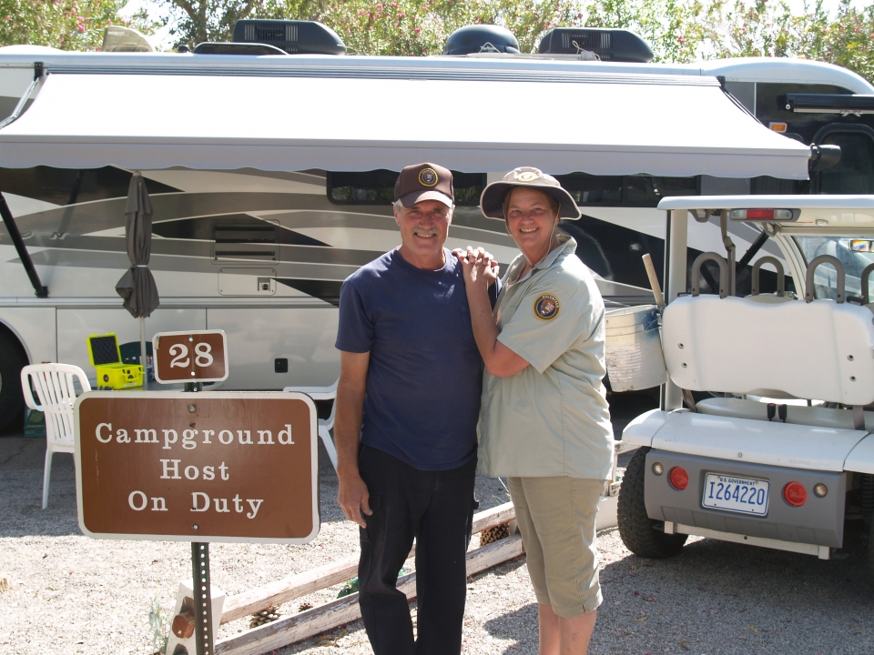 Volunteer campground hosts pose for a photograph in a campground parking lot