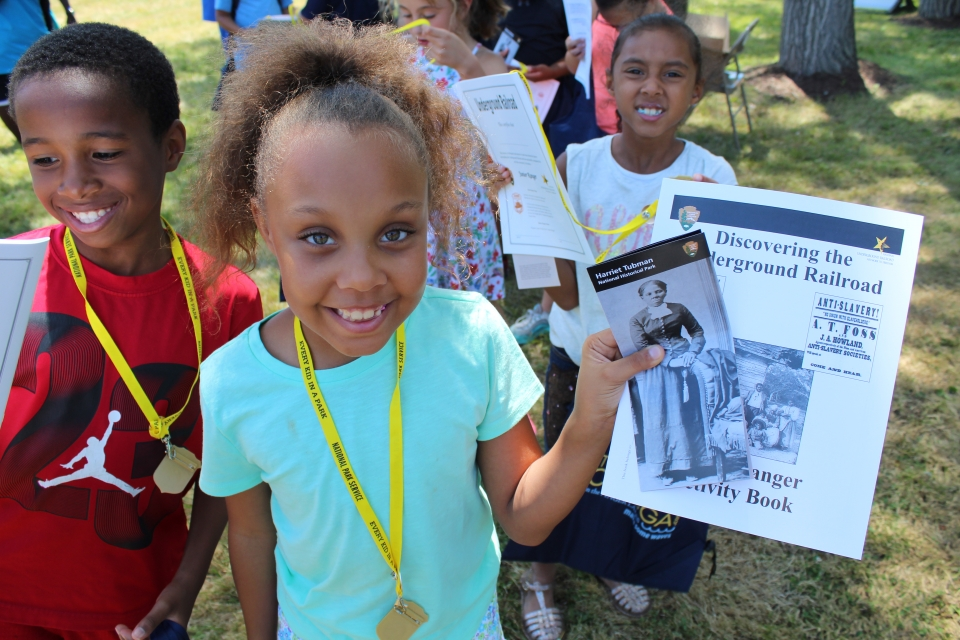 A smiling young girl holds up her junior ranger activity book