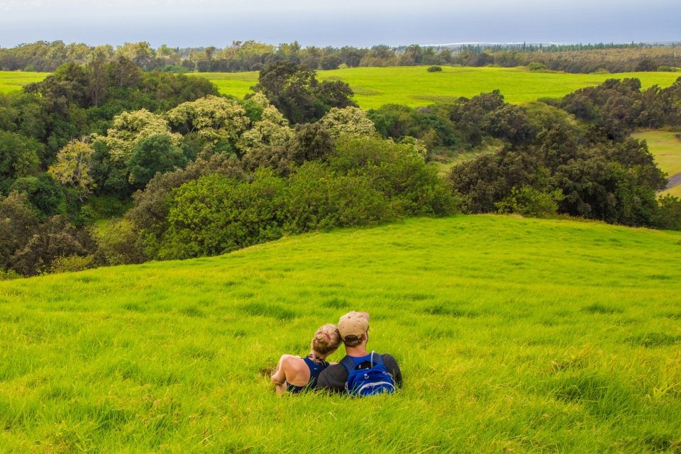 Two hikers rest on a grassy hill