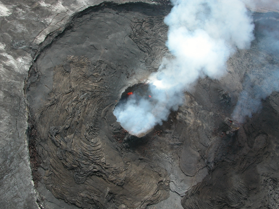 Aerial view of a volcano crater with lava and smoke coming out of the top at Hawaii Volcanoes National Park.