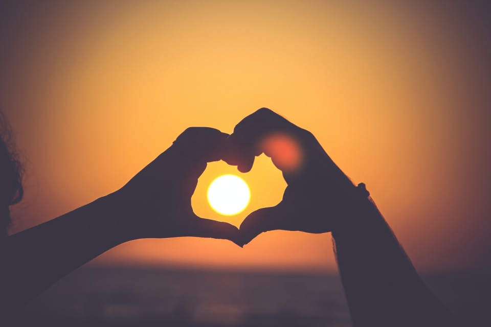 Two hands make a heart in the sun