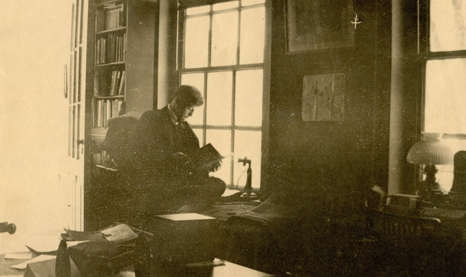 Young man sitting in front of window reading