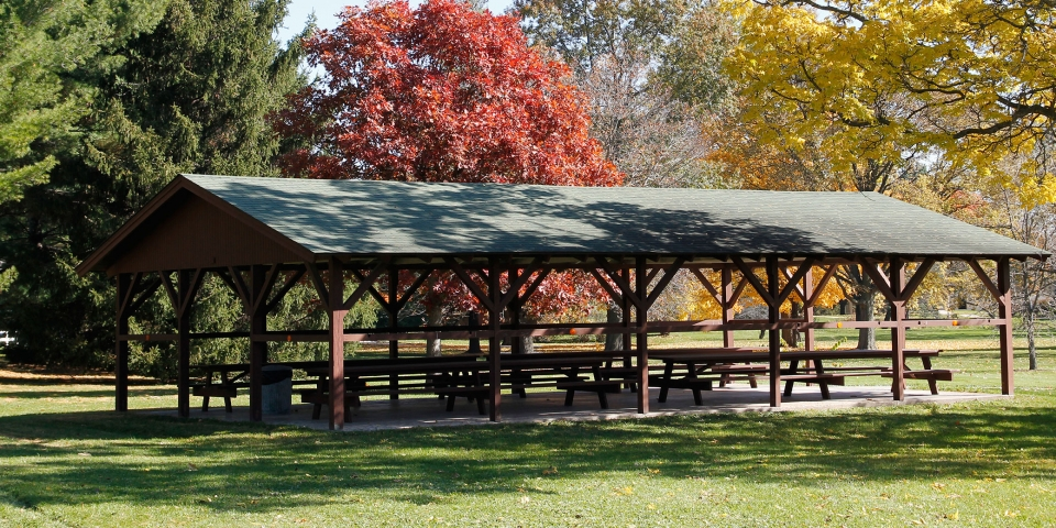 green and brown wooden picnic shelter with picnic tables at Herbert Hoover National Historic Site