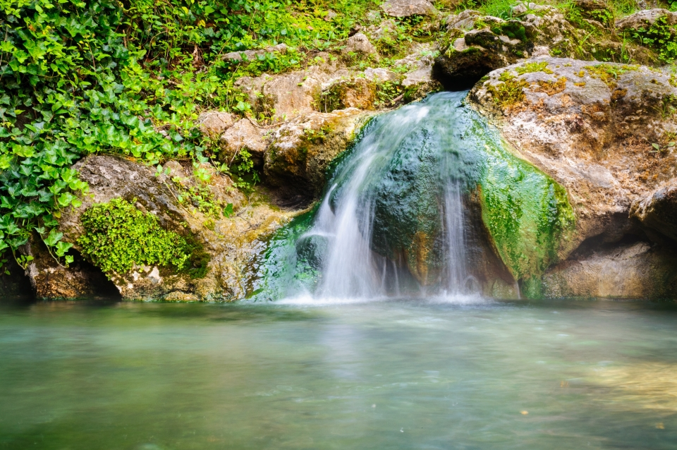 Waterfall cascading into a warm spring over boulders covered in greenery at Hot Springs National Park.