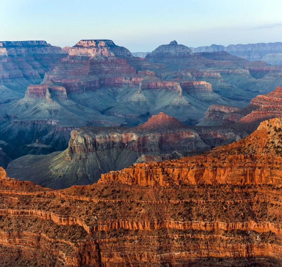 Sunset illuminating the striated red rock cliffs at the Grand Canyon