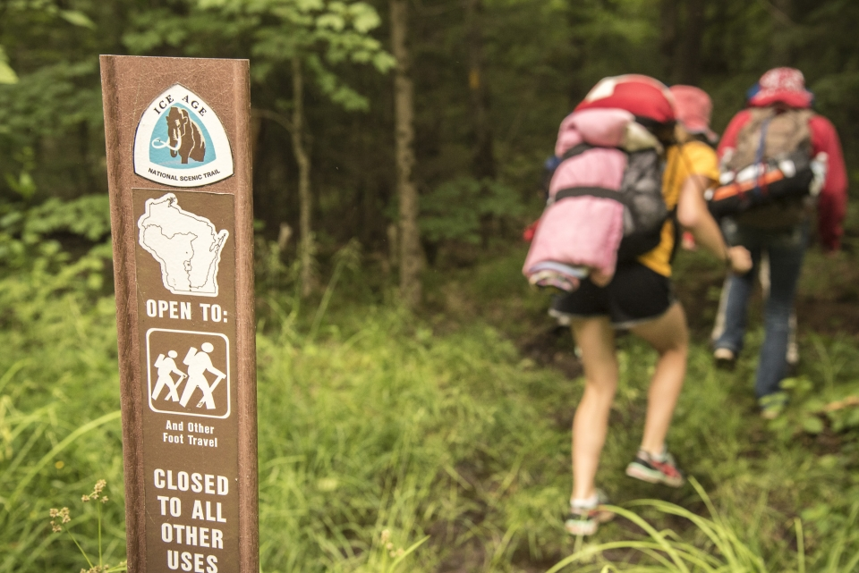 "Hikers make their way past a signpost reading ""Ice Age National Scenic Trail"""