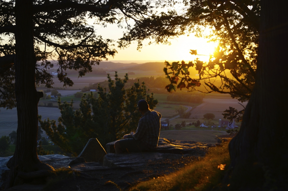 A man sits on a rock, framed by leafy trees, looking out at the setting sun and fields below.
