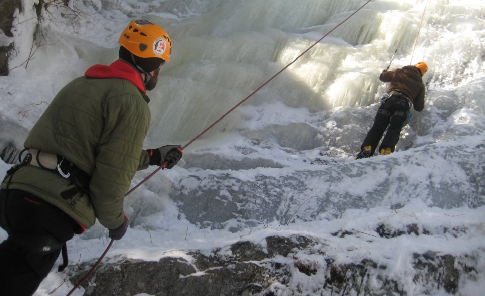 One person wearing a helmet belaying another person ice climbing up a frozen waterfall.