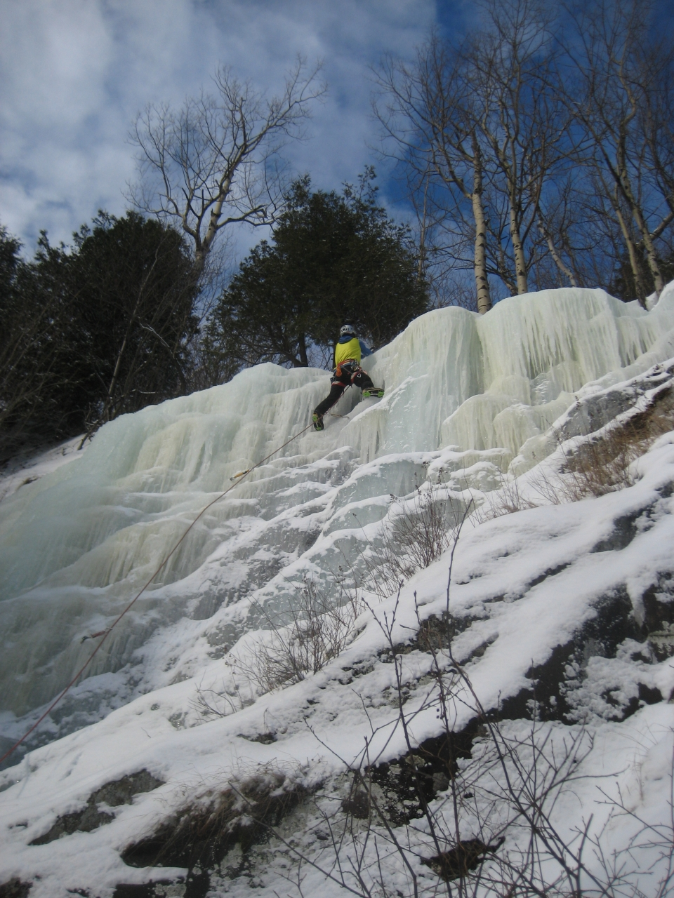 Person leading and ice climb up a frozen waterfall