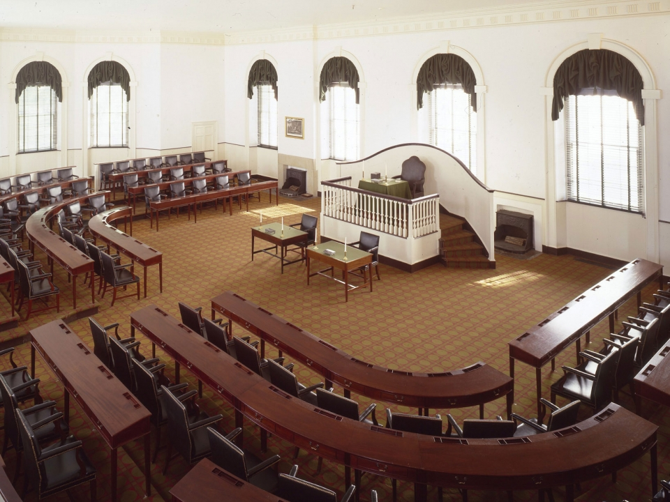 Color photo showing three rows of desks and chairs in a semi-circle facing a raised dais.