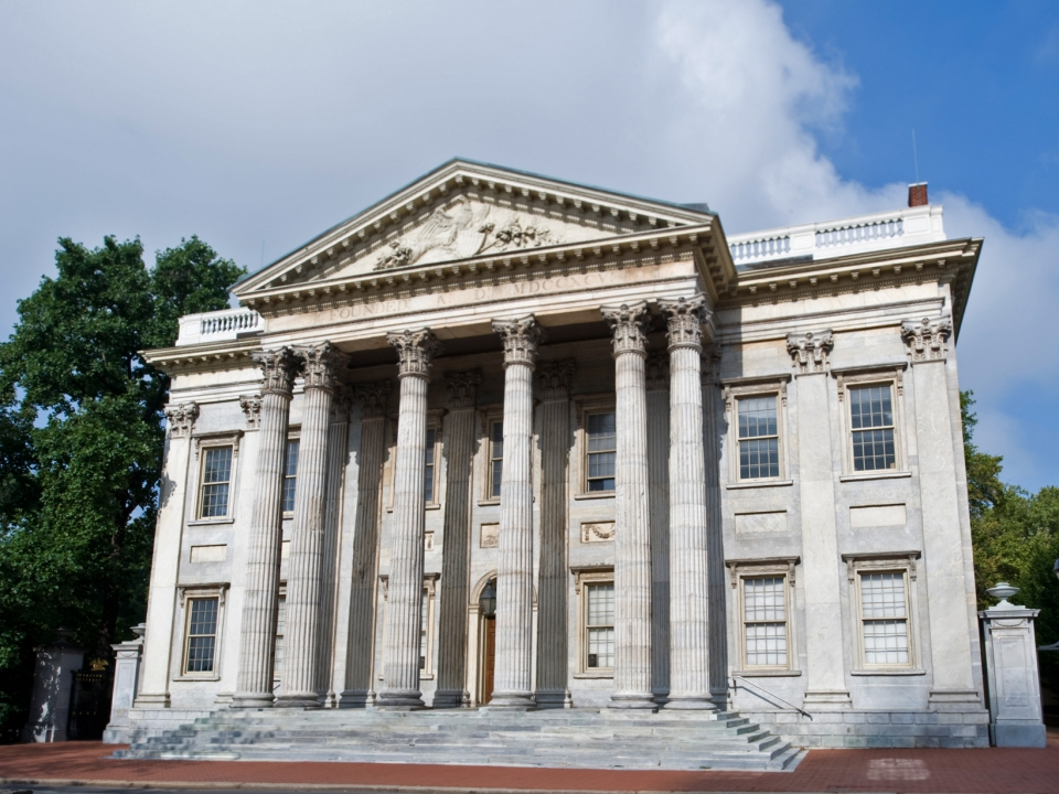 Facade of a federal style building with white stone columns and gently sloping steps upwards to the door