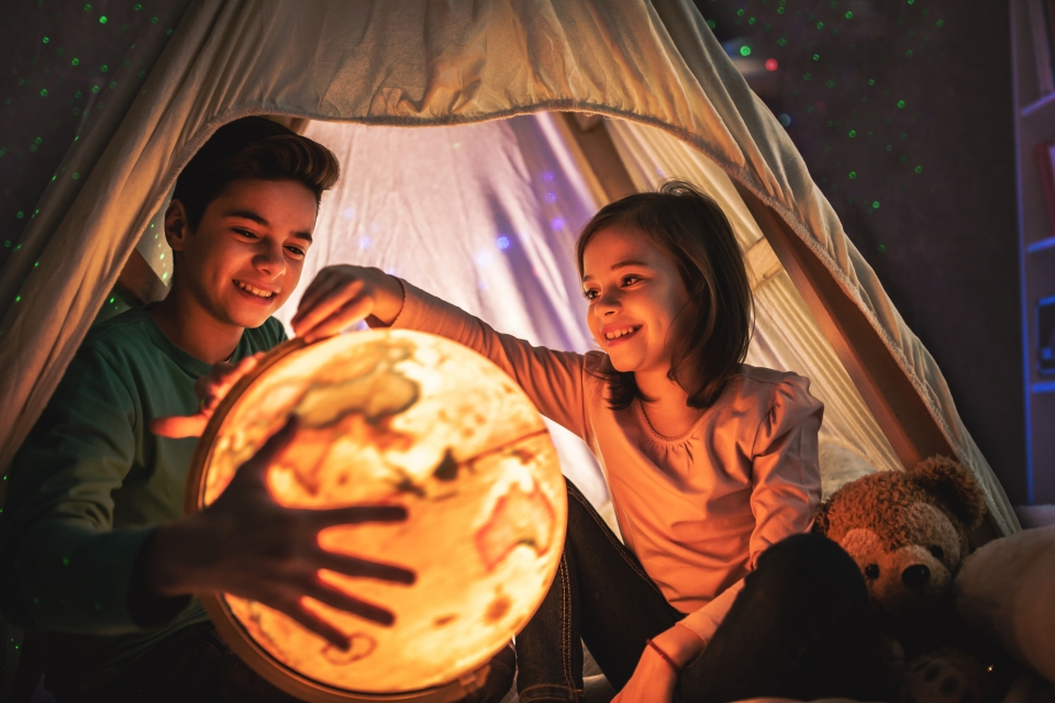 Two young children sit in an illuminated tent, set up indoors. They smile and point at a glowing globe.