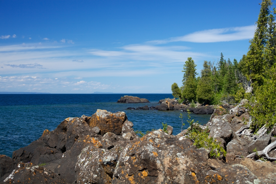 Beyond the shoreline rocks, bright blue water rests in Hugginin Cove at Isle Royale National Park.