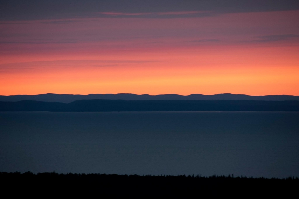 A colorful orange, red, and purple sunset behind the hills and the lake at Isle Royale National Park