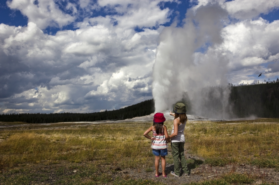 two children looking at a spouting geyser