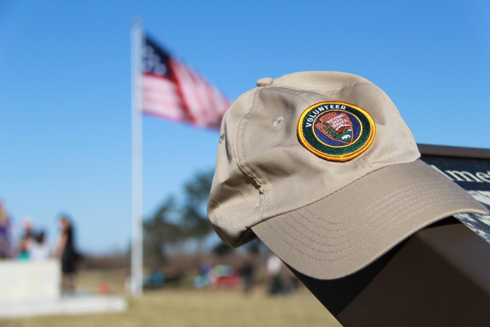 Close-up of a tan NPS Volunteer hat sitting on a sign at Jean Lafitte National