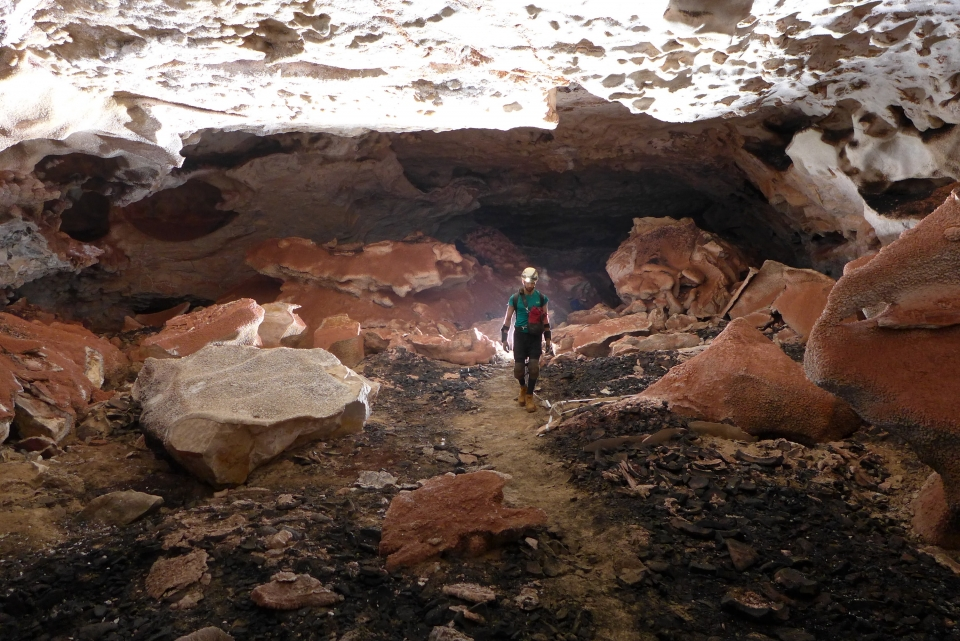 A caver with a helmet and headlamp walking through a brightly lit cave near Crushing Deep at Jewel Cave National Monument