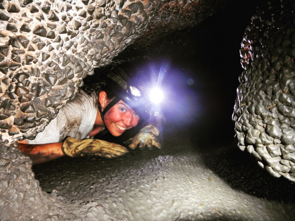 Riley Hays wearing a hard hat and head lamp crawling through Jewel Cave National Monument