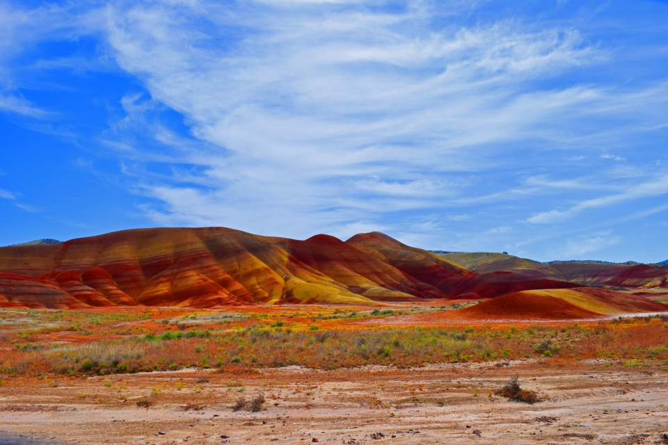 Under a bright blue sky with wispy clouds, layers of red, orange, and yellow make up the Painted Hills at John Day Fossil Beds National Monument.