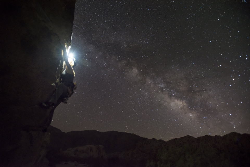 A rock climber climbing at night with a headlamp with the Milky Way in the background at Joshua Tree National Park
