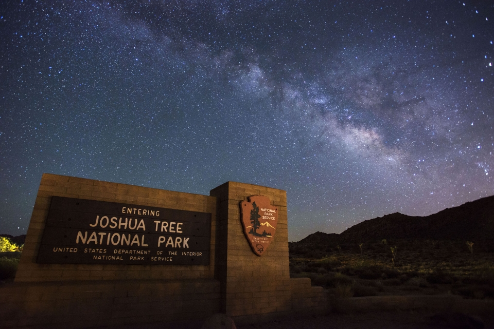 """Night sky scene shows the Milky Way galaxy arching over the """"entering Joshua Tree National Park"""" entrance sign"""