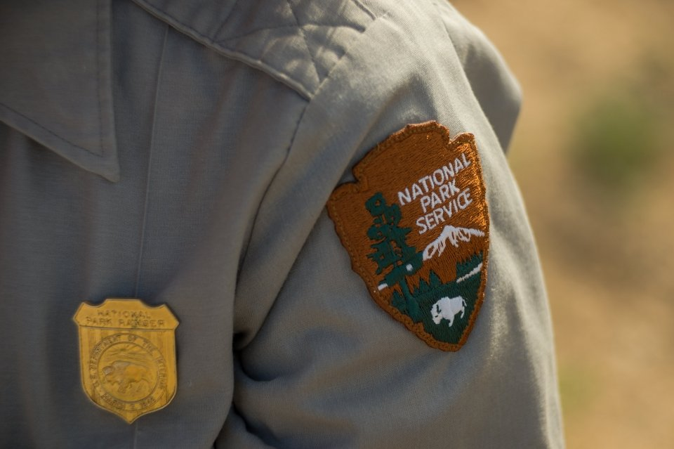 Close-up of a National Park Service badge and patch on an employee