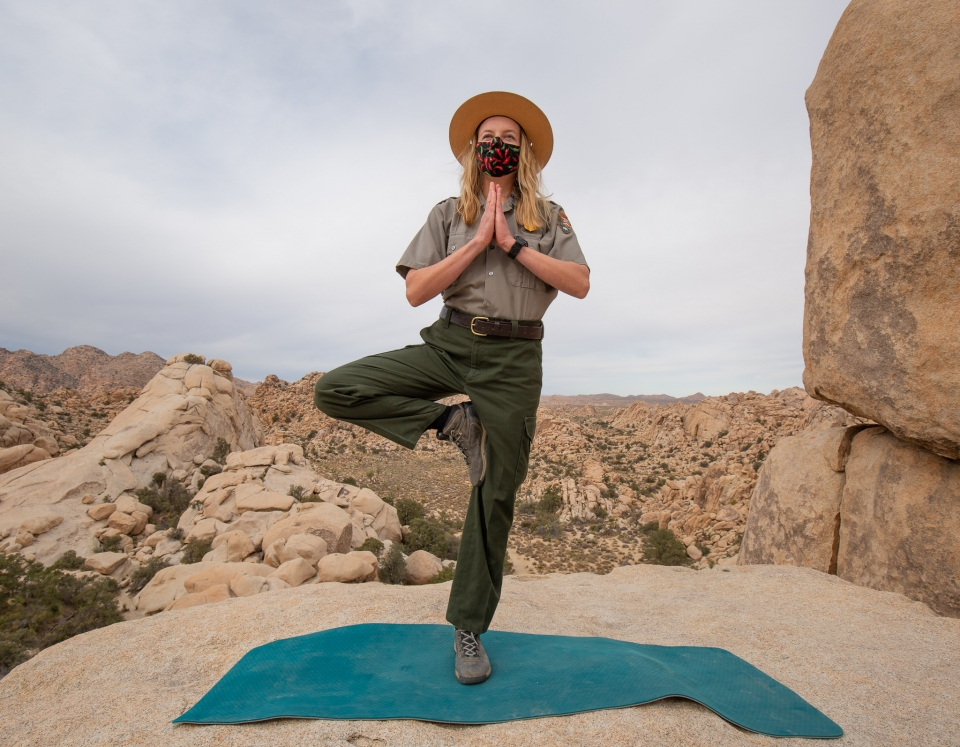 A park ranger in uniform with a flat hat on a rock with Joshua Trees in the background. They are in a yoga pose with one foot on the rock and the other lifted on their thigh. Their arms in a prayer position underneath their chin.