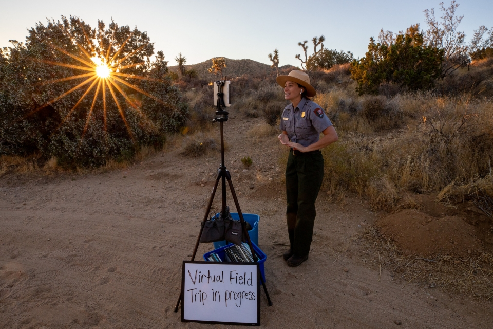 A ranger stands in front of a tablet and a sign that reads 'Virtual Field Trip in Progress'