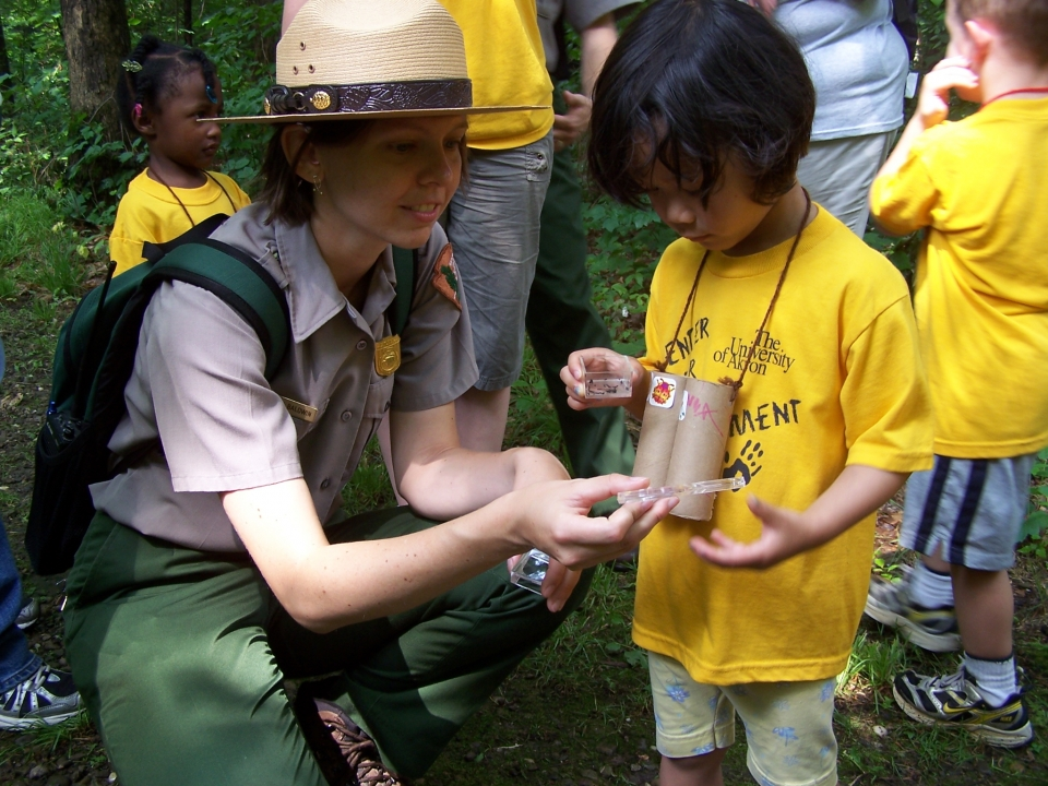 Park Ranger looking at a bug box with kids in the forest