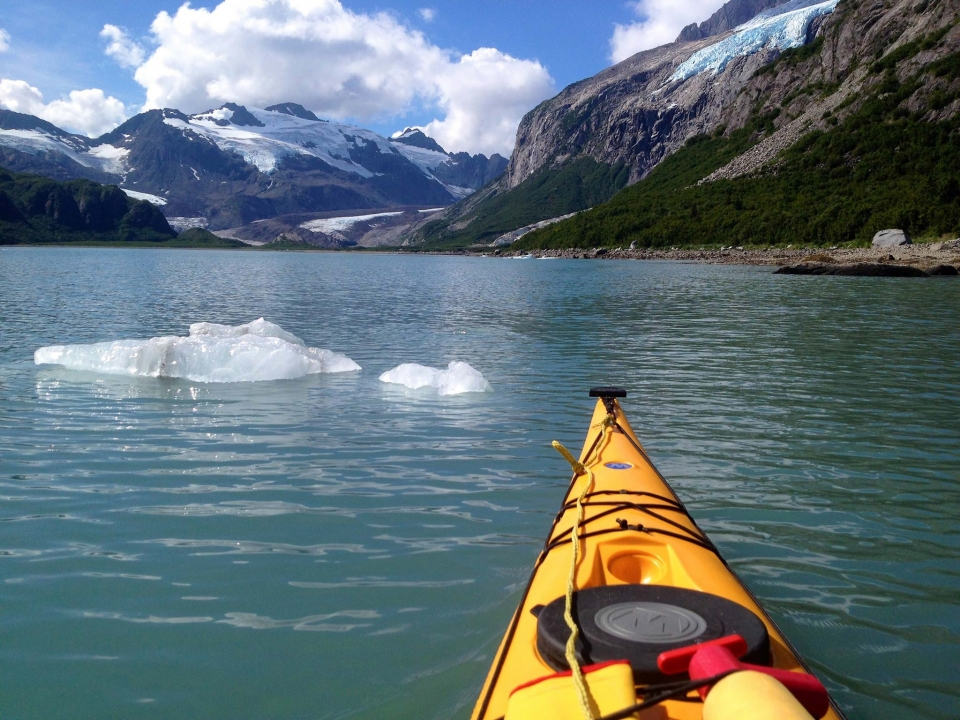 Front of a yellow kayak in the blue waters of Kenai Fjords National Park with mountains and glaciers in the horizon