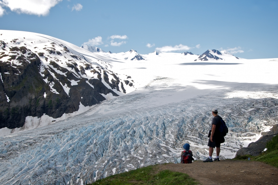 Two people stand next to a dirt trail, looking across Exit Glacier and the Harding Icefield; Kenai Fjords National Park