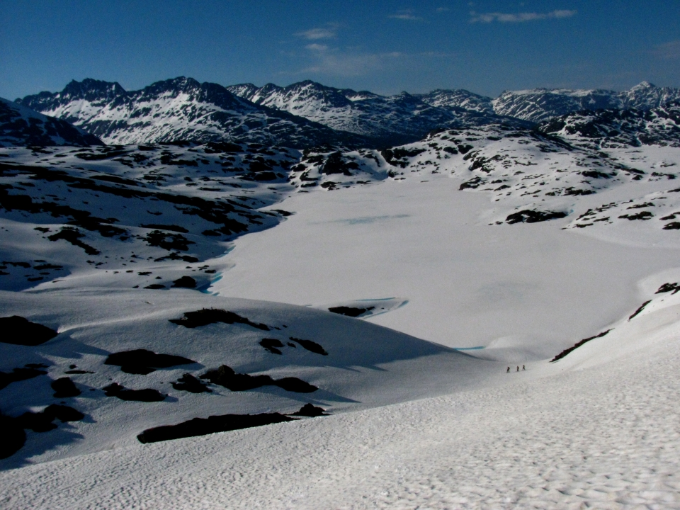 View of high alpine terrain with rocky peaks in the distance and snow fields in the foreground