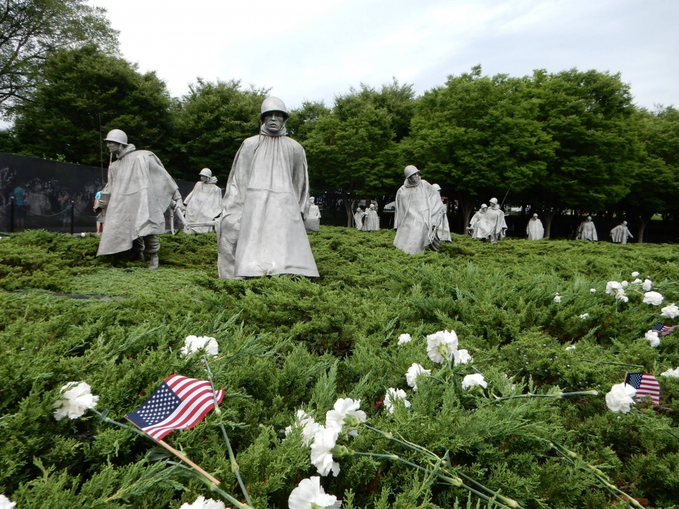 White carnations and small American flags on the bushes in front of the metal statues of the Korean War Veterans Memorial at the National Mall & Memorial Parks in Washington, DC