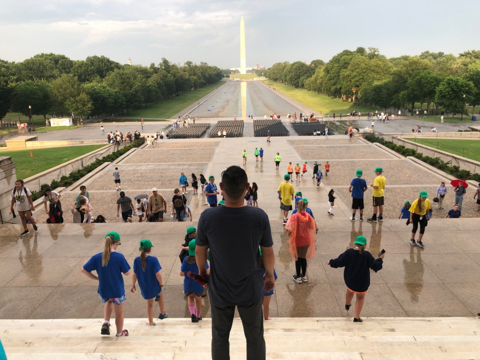 Kyle Funakoshi stands on the steps of the Lincoln Memorial, looking out toward the Washington Monument