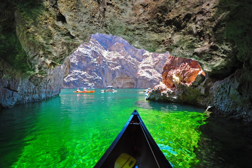 Kayakers traveling through the stunning green waters of Emerald Cave at Lake Mead National Recreation Area.